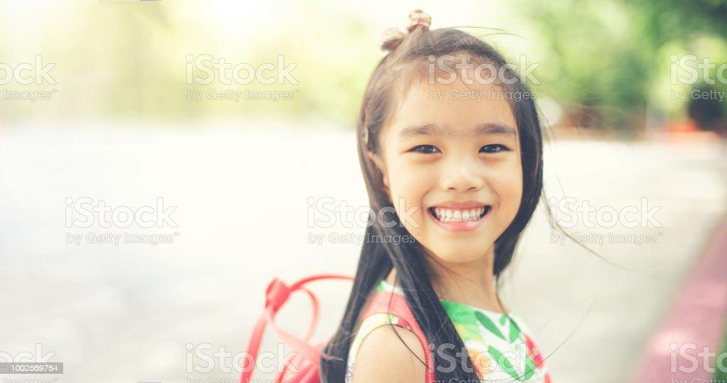 voltar para a escola. Menina feliz e sorridente do ensino fundamental no pátio da escola. - foto de acervo