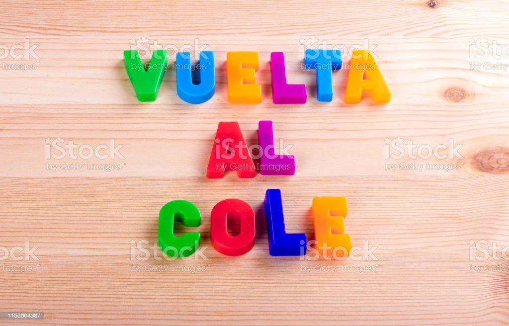 """Regreso a la escuela en español, """"vuelta al cole"""". Texto escrito con letras de color magnético sobre una mesa de la escuela de madera - Foto de stock de Andar en bicicleta libre de derechos"""