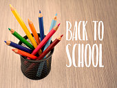 Colored pencils in a cup images. Art supplies on a wooden background. School supplies for drawing. Back to School lettering with crayons images