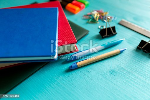 istock Back to school. Items for the school on a blue wooden table. 879166084