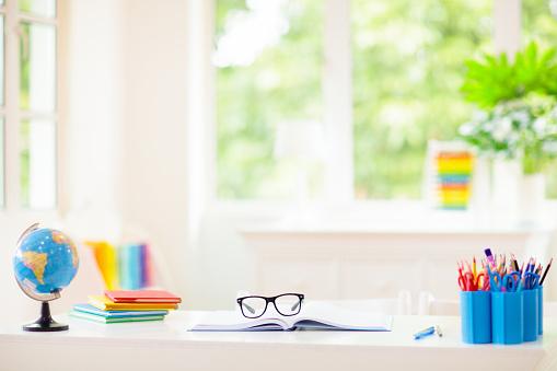 istock Back to school. Kids desk with books, globe. 1165009048