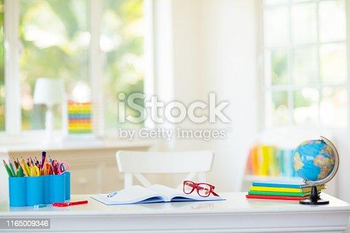istock Back to school. Kids desk with books, globe. 1165009346