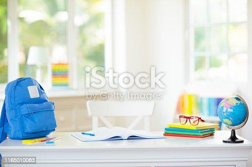 istock Back to school. Kids desk with books, globe. 1165010083