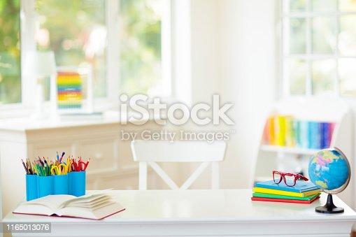 istock Back to school. Kids desk with books, globe. 1165013076