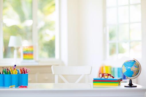istock Back to school. Kids desk with books, globe. 1165013111