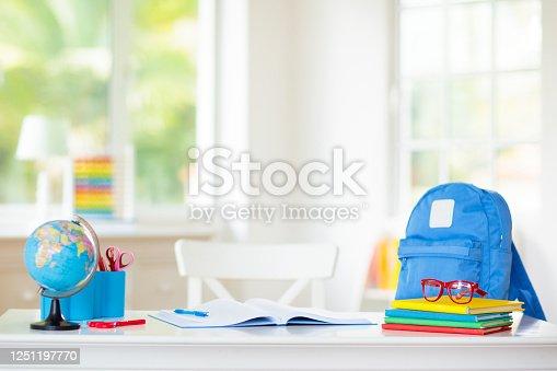 istock Back to school. Kids desk with books, globe. 1251197770