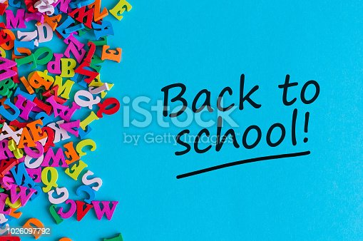 istock Back to school - Message at blue background with many little color letters. Education concept, 1 september time 1026097792