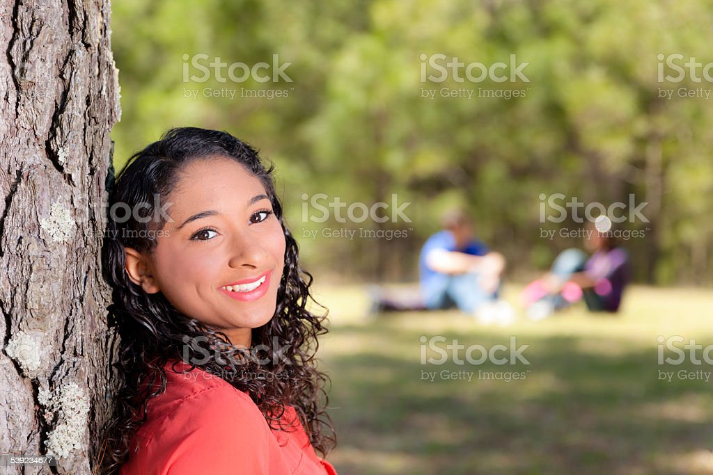 Back to School: Mixed-race girl on school campus. Friends background. royalty-free stock photo