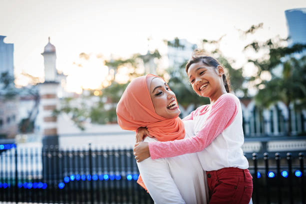Back to school - mother preparing daughter for school and sharing love Malaysian Muslim mother with two daughters spending relaxing afternoon after school islam stock pictures, royalty-free photos & images