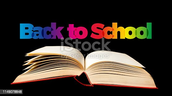 istock Back to school. Open book on black background. Text 1149078848