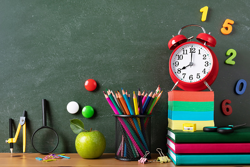 1045293630 istock photo Back to school or education concept with alarm clock, green apple and school supplies against blackboard on wooden table. 1263320464