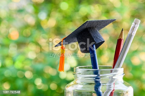 istock Back to school or graduate certificate program concept : Black graduation cap on a pencil in a bottle. Back to school is the period in which students prepares school supply for upcoming school year. 1081792548