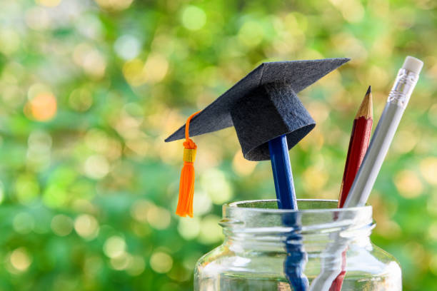 Back to school or graduate certificate program concept : Black graduation cap on a pencil in a bottle. Back to school is the period in which students prepares school supply for upcoming school year. Back to school or graduate certificate program concept : Black graduation cap on a pencil in a bottle. Back to school is the period in which students prepares school supply for upcoming school year. enrollment stock pictures, royalty-free photos & images