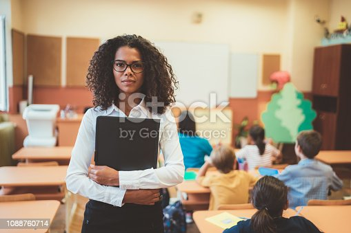 Portrait of mixed race teacher in class standing serious during exam