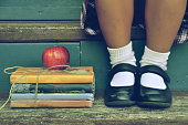 Little girl sitting on stairs next to school books and apple.