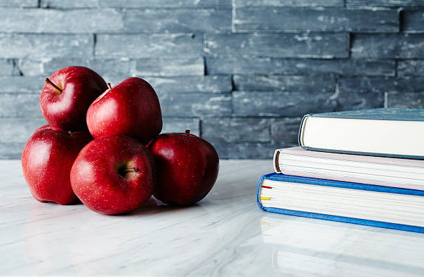 Back to School Back to School - Stack of fresh red apples on marble countertop. Hardcovered books standing on the right side. red delicious apple stock pictures, royalty-free photos & images