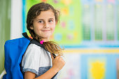 An Ethnic elementary school girl is indoors in a classroom. It is the first day of school. The girl is wearing casual clothing and a backpack, and she is smiling at the camera while standing in front of the chalkboard.