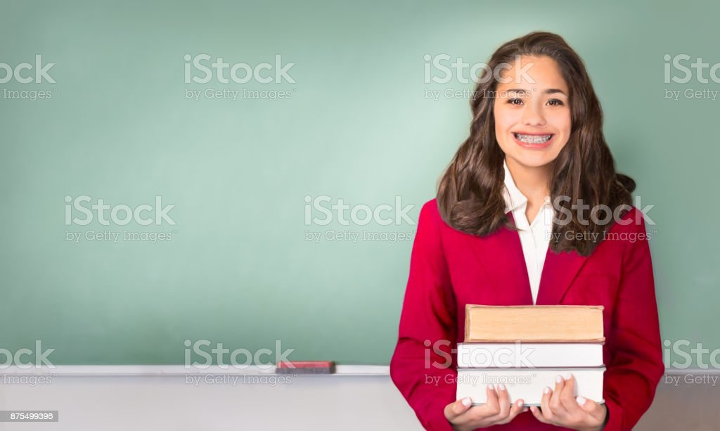 Back to School. Pretty ethnic or Hispanic teen in Front of Chalk stock photo