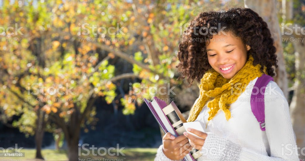 Back to School. Pretty Young Female Student with Mobile Phone stock photo