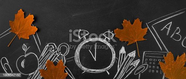 istock Back to school. School accessories chalked on the blackboard Banner 1009342152