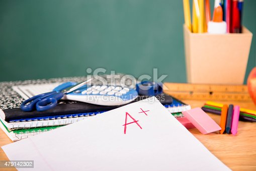 istock Back to school. School supplies, A+ paper on desk. Education. 479142302