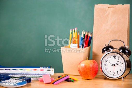 istock Back to school school supplies, apple, alarm clock on desk. 589956950