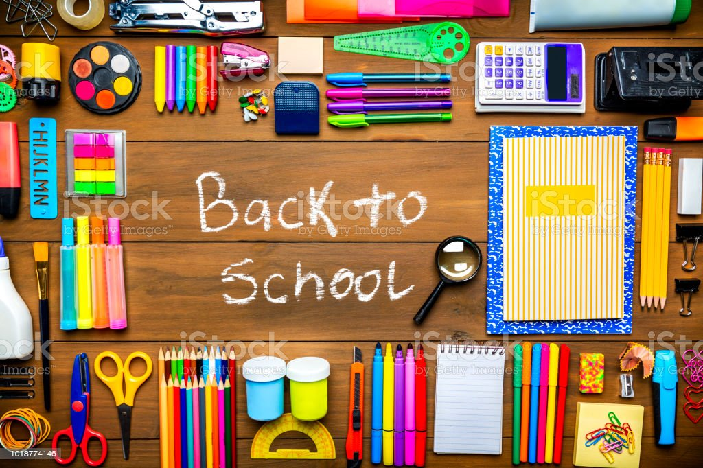 Back to School sign in overhead shot of wood table with frame of school office supplies stock photo
