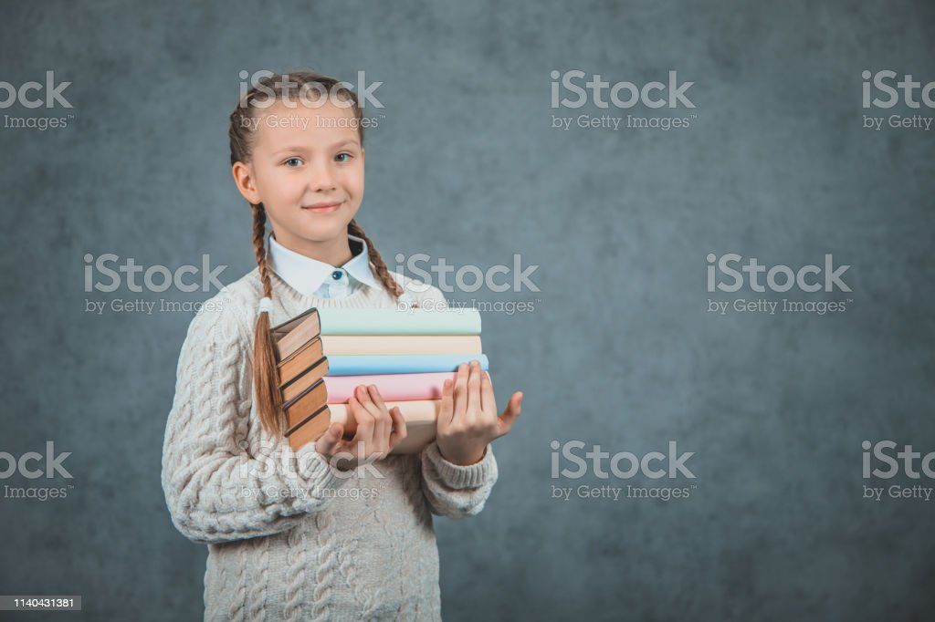 Back to school! Smiling schoolchild holds books. Kid is ready for...