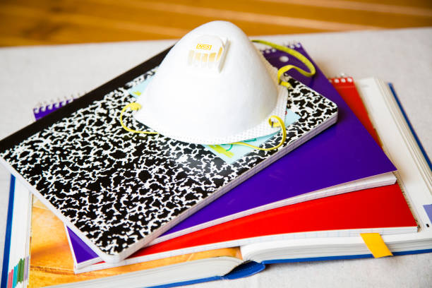 Back to school stack of book and spiral notebooks. Stack of an open book, spiral notebooks and ledger. N-95 covid-19 mask on top of stack of books. covid-19 stock pictures, royalty-free photos & images