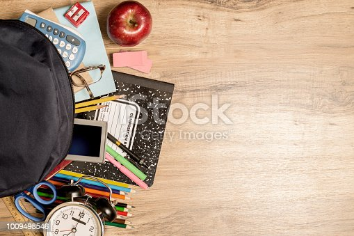 istock Back to school supplies on wooden student desk. 1009498546