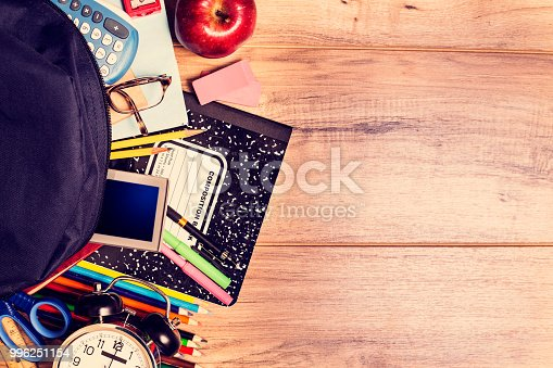 istock Back to school supplies on wooden student desk. 996251154