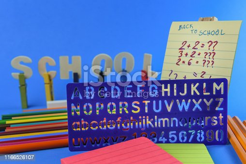 Conceptual photography of back to school theme - school supplies on a blue background surface - close up photography