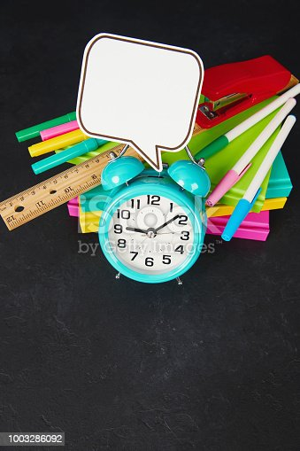 Back to school supplies with alarm clock and vibrant books and pens