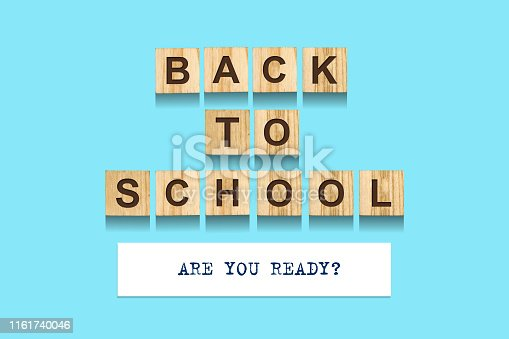 istock Back to school. The word is written from the alphabet on wooden blocks. Blue background. 1161740046