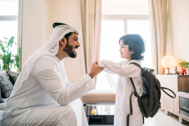 Back to school time: arab dad saying hello to his son stock photo