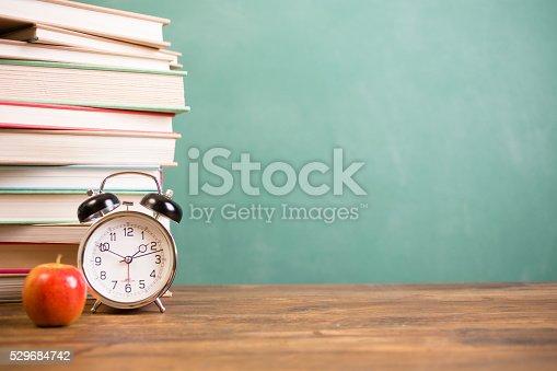 istock Back to school time. Education. Textbooks, alarm clock, chalkboard. 529684742
