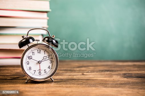 1045293630istockphoto Back to school time. Education. Textbooks, alarm clock, chalkboard. 529998874