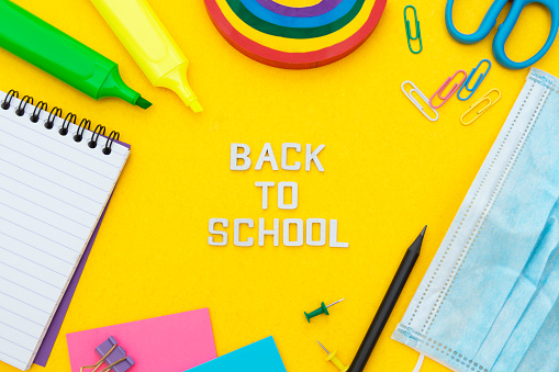 istock Back to school words. Face mask, colorful pencils, rainbow eraser, notebook, sticky notes and office supplies. Flat lay. Abstract educational background. 1266749137