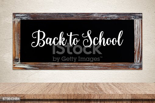 istock Back to school words on vintage chalkboard over empty table background, education concept, template 675643484
