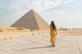 Rear view of a female tourist enjoying a tour to the Pyramids of Giza in Egypt.