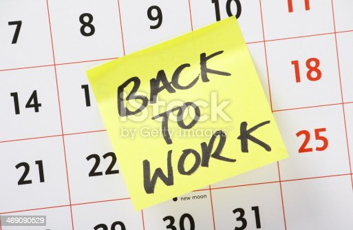 The phrase Back to Work written on a yellow paper sticky note an stuck to a wall calendar background