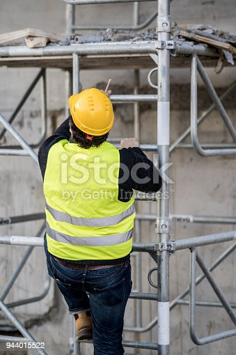 Back turned construction worker climbing a ladder up to the scaffolding