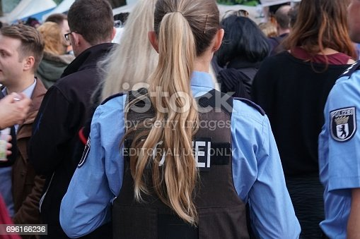 istock Back turned female police officer at work during a street parade 696166236