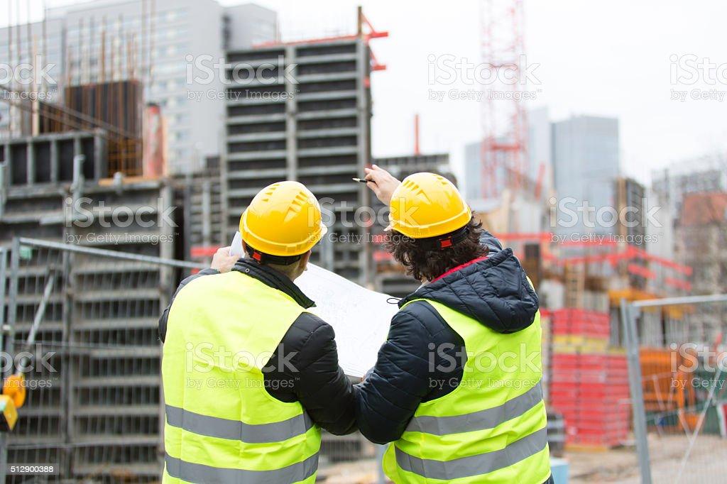 Rückseite aus Arbeiter, die auf der Baustelle Pläne überprüfen. – Foto