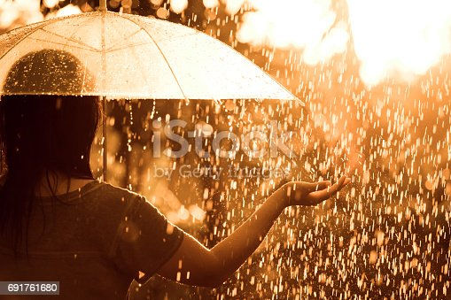 istock Back veiw of woman  with umbrella in the rain and sunlight 691761680