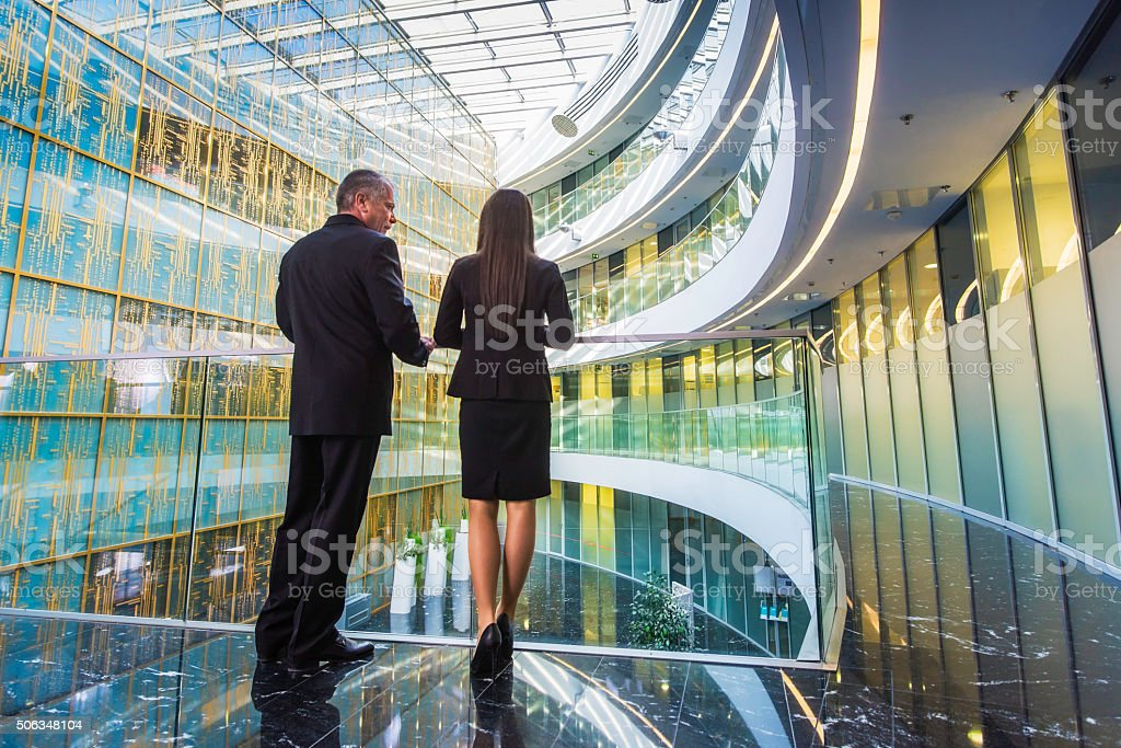 Back vieew of businessman and businesswoman in modern glass building stock photo