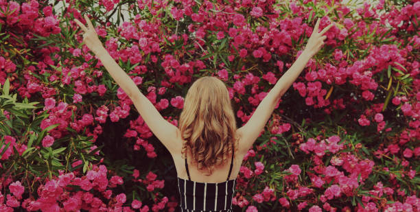 Back view beautiful happy woman raising her hands up in a garden on roses flowers background stock photo