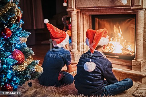 865399512 istock photo Back view, brother and sister wearing Santa's hats warming next to a fireplace in a living room decorated for Christmas. 1135144141