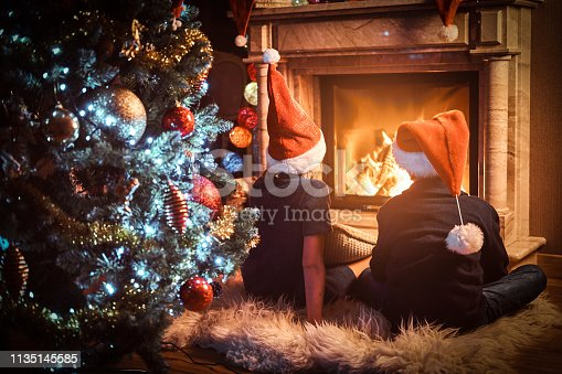865399512 istock photo Back view, brother and sister wearing Santa's hats warming next to a fireplace in a living room decorated for Christmas. 1135145585