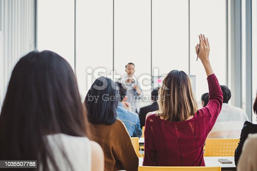 istock Back view business woman raising hand for asking speaker for question and answer concept in meeting room for seminar 1035507788
